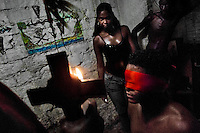 A young Cuban man, wearing a red blindfold, passes a secret initiation ritual of the Palo Monte religion in Santiago de Cuba, Cuba, August 1, 2009. The Palo religion (Las Reglas de Congo) belongs to the group of syncretic religions which developed in Cuba amongst the black slaves, originally brought from Congo during the colonial period. Palo, having its roots in spiritual concepts of the indigenous people in Africa, worships the spirits and natural powers but can often give them faces and names known from the Christian dogma. Although there have been strong religious restrictions during the decades of the Cuban Revolution, the majority of Cubans still consult their problems with practitioners of some Afro Cuban religion.