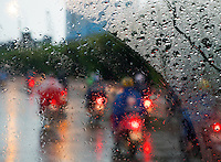 Motorbikes and scooters during a heavy tropical rain shower a common sight in the yearly Monsoon Season on a Highway near Saigon. Ho Chi Minh City, Vietnam