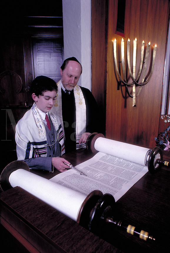 Boy reads from Torah with rabbi