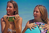 Teenage girls laughing and eating watermelon at the beach.