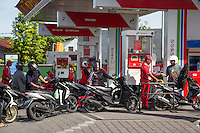 Bali, Indonesia.  Motorbikes Lining up for Fuel at Gas Station.