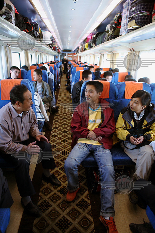 Chinese tourists relax during a train journey along the Qingzang (Qinghai?Tibet) railway. Travelling at altitudes exceeding 4000m, the controversial Qinghai?Tibet line is the world's highest railway. It is also the first rail track to link the People's Republic of China with Tibet. .
