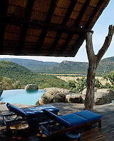 A pair of sun-loungers are placed in the shade beside one of three swimming pools at the lodge overlooking the spectacular landscape