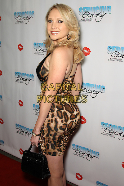 """ALANA CURRY.Cast and friends of the hit Fox Reality series,  """"Seducing Cindy,"""" arrive to the finale party at Guy's North. Studio City, CA, USA. .March 18, 2010.half 3/4 length brown black leopard print dress back behind rear looking over shoulder bag purse  .CAP/CEL.©CelPh/Capital Pictures."""
