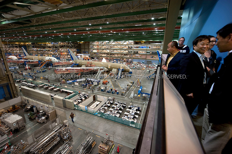 10/22/2009--Everett, WA, USA..At Boeing's Everett, Wash., the first Boeing 787s are under production, destined for Japan's ANA airlines. Here tourists can view the production line...The 787-8 Dreamliner will carry 210 - 250 passengers on routes of 7,650 to 8,200 nautical miles (14,200 to 15,200 kilometers), while the 787-9 Dreamliner will carry 250 - 290 passengers on routes of 8,000 to 8,500 nautical miles (14,800 to 15,750 kilometers).  A third 787 family member, the 787-3 Dreamliner, will accommodate 290 - 330 passengers and be optimized for routes of 2,500 to 3,050 nautical miles (4,600 to 5,650 kilometers). ..In addition to bringing big-jet ranges to mid-size airplanes, the 787 will provide airlines with unmatched fuel efficiency, resulting in exceptional environmental performance. The airplane will use 20 percent less fuel for comparable missions than today's similarly sized airplane. It will also travel at speeds similar to today's fastest wide bodies, Mach 0.85. Airlines will enjoy more cargo revenue capacity. Passengers will also see improvements with the new air...©2009 Stuart Isett. All rights reserved.