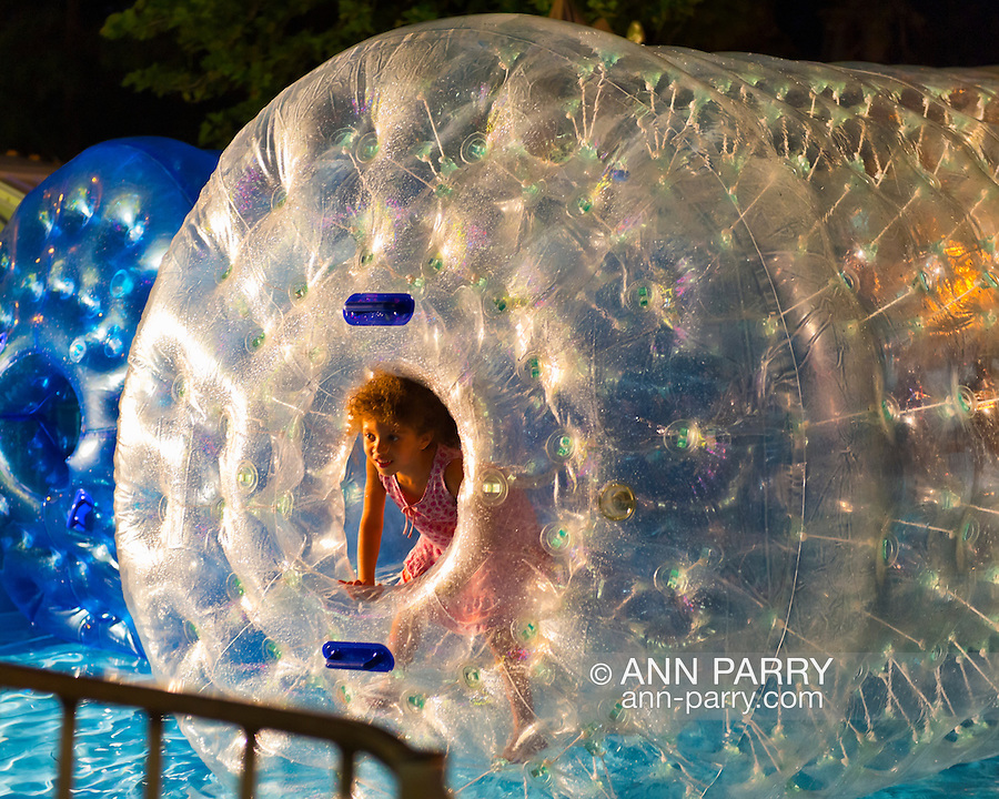 Young girl looks out from the entrance of a Bobbles roller tube on water, during the first night of the annual Herricks Community Fund Spring Carnival, which raises funds for programs that enrich the community and school district. The Long Island carnival runs through June 2.