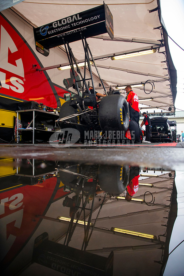 May 20, 2018; Topeka, KS, USA; The car of NHRA top fuel driver Doug Kalitta reflects in a rain puddle in the teams pit area during a delay to the Heartland Nationals at Heartland Motorsports Park. Mandatory Credit: Mark J. Rebilas-USA TODAY Sports