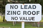 No Lead Zinc Roof No Value sign outside church to deter potential thieves who target churches for their lead roofs, Ellingham, Norfolk, England, UK