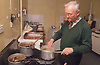 Elderly man cooking in day centre kitchen,