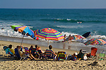 People under colorful shade umbrellas on sand beach in summer, Carlsbad, San Diego County coast, California