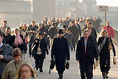 Commuters cross London Bridge on their way to work in the City of London financial district.