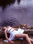 Young woman in white dress tied with red bondage ropes lying on a shore of a lake near water.