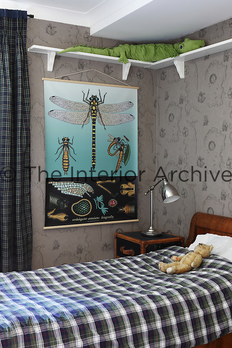 A child's bedroom is papered with historical map wallpaper featuring ships and compasses. A large dragonfly print hangs on the wall next to the bed with Ralph Lauren bedding.