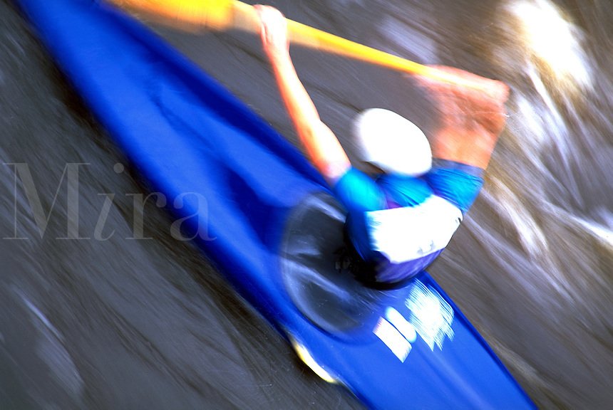 Blurred motion image of a kayaker negotiating some river rapids.
