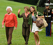First lady Laura Bush waves to onlookers as she walks with former first lady Barbara Bush (L) and daughter Barbara as they arrive at the White from a weekend at the Crawford, Texas ranch, 11 May 2008 in Washington, DC.  United States President George W. Bush, whose daughter Jenna married Henry Hager at the ranch, described the experience as 'spectacular' and 'it's all we could have hoped for'.   <br /> Credit: Mike Theiler / Pool via CNP