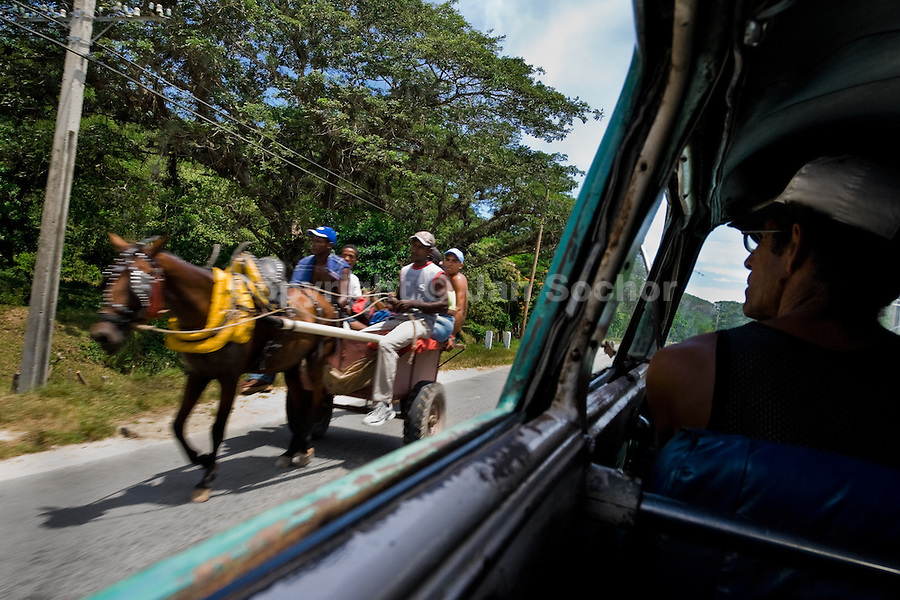 A horse drawn cart passes against the car on the country road, close to Santiago de Cuba, Cuba, 2 August 2008. About 50 years after the national rebellion, led by Fidel Castro, and adopting the communist ideology shortly after the victory, the Caribbean island of Cuba is the only country in Americas having the communist political system. Although the Cuban state-controlled economy has never been developed enough to allow Cubans living in social conditions similar to the US or to Europe, mostly middle-age and older Cubans still support the Castro Brothers' regime and the idea of the Cuban Revolution. Since the 1990s Cuba struggles with chronic economic crisis and mainly young Cubans call for the economic changes.