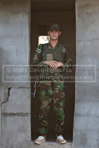 29/06/2014. Khanaqin, Iraq. A Kurdish peshmerga fighter stands in the doorway of a sentry post at a Kurdish peshmerga base in Khanaqin, Iraq.<br /> <br /> The peshmerga, roughly translated as those who fight, is at present engaged in fighting ISIS all along the borders of the relatively safe semi-automatous province of Iraqi-Kurdistan. Though a well organised and experienced fighting force they are currently facing ISIS insurgents armed with superior armament taken from the Iraqi Army after they retreated on several fronts. &copy; Matt Cetti-Roberts