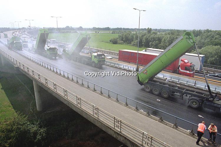 Foto: VidiPhoto..RENKUM - De werkzaamheden aan de Rijnbrug (A50) bij Heteren zijn de laatste fase ingegaan. Vrijdag is gestart met het aanbrengen van de asfaltlaag. De reconstructie van de belangrijke verbindingsbrug is op 2 juli begonnen en zorgt dagelijks voor grote verkeersoverlast. De 1e fase moet op 18 augustus klaar zijn. Volgend jaar tijdens de zomervakantie wordt de andere helft van de brug onder handen genomen. De reconstructiewerkzaamheden kosten ongeveer 8 miljoen gulden..