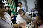 Dr. James Brandt, of Sacramento, listens as a patient's words are translated into English during a screening day for glaucoma patients at the Ho Chi Minh City Eye Hospital on Monday, April 14, 2008.  Kevin German /  kevin@kevingerman.com..ORBIS Flying Eye Hospital brought doctors, nurses and specialists from all over the world to Ho Chi Minh City, Vietnam from April 7-18, 2008.  The ORBIS program contributed to the efforts of Ho Chi Minh City Eye Hospital in fighting avoidable blindness by educating local ophthalmologists to diagnose and manage pediatric blindness, retinal disease, oculoplastics, and blindness due to glaucoma.