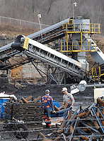 Workers remove equipment in the yard Monday, Jan. 9, 2006,  at the Sago mine near Buckhannon, WV, where 12  miners were killed in an explosion. (Gary Gardiner/EyePush Newsphotos)<br />