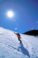 Man with raised arm in triumph snowboards down the slope of Mauna Kea. Starburst white sun and observatory highlight the background.