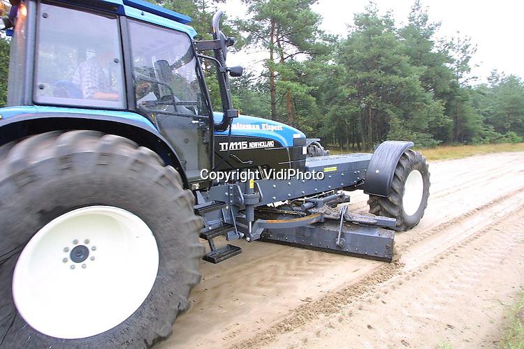 Foto: VidiPhoto..'t HARDE - Met een voor Nederland nieuwe tractor (New Holland TM 115) worden op de schietterreien van defensie in  't Harde de zandwegen geegaliseerd. De tot 7 meter verlengde tractor is zowel aan de onderzijde als aan de bovenzijde bepantserd en heeft aan de voorzijde pantserglas van 3,5 cm. dik. De zes cilinder motor heeft een vermogen van 120 pk. De schakeling werkt via een joystick. De bepantsering is nodig als bescherming tegen niet-ontplofte munitie. Eigenaar is Evert Schuiteman uit Elspeet. (06-51828256)