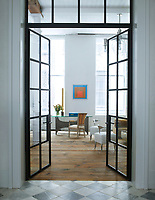 A view through a pair of internal French doors into the library. The Philippe Starck chairs were prototypes for the Royalton Hotel. The 18th-century floorboards were salvaged from a Pennsylvania farmhouse. A 1966 table by Philippe Hiquily is paired with a Louis XVI fauteuil with its original upholstery.