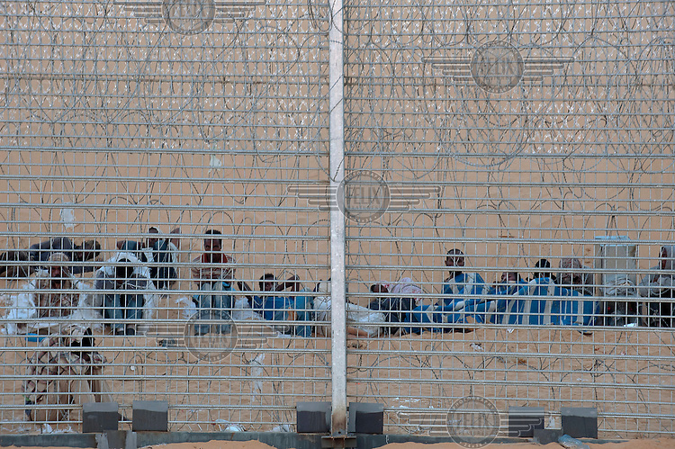 Eritrean immigrants sit on the ground behind a newly-built fence on Israeli/Egyptian border. They arrived a week earlier, crossed the old fence but got trapped by the new one. Israeli soldiers have been providing the group with water, but not allowing them into Israel. After eight days the Israeli government partially relented and allowed entrance for two women and one youth, while the rest of men returned to Egypt.