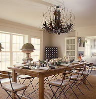 The long dining table is surrounded by antique metal  folding chairs and lit from above by a chandelier made from natural twigs and branches whilst a floor covering of seagrass emphasises the rustic feel