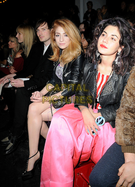 DAN GILLESPIE-SELLS, NICOLA ROBERTS & MARINA DIAMANDIS of Marina And the Diamonds .At the House of Holland a/w 2011 Fashion Show during London Fashion Week, Old Sorting Office, London, England, UK, February 19th 2011..half length sitting pink dress black jacket leather shoes girls aloud front row  .CAP/CAN.©Can Nguyen/Capital Pictures.