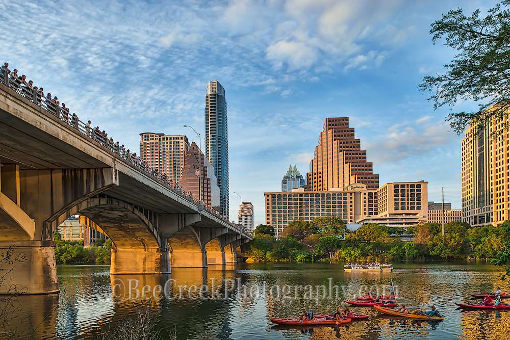 This is an image from the Ladybird Hike and Bike trail of the anticipated bats coming out from under the Congress Bridge in Austin, with the crowds of people on the bridge and below all waiting for their nightly appearance. The lighting was very good this day with a nice reflection under the bridge along with some nice clouds and blue skies. These mexican freetail bats have made their home under the bridge for more than forty years and the estimated number is somewhere around 1.5 million of them.  It is an amazing site to see.