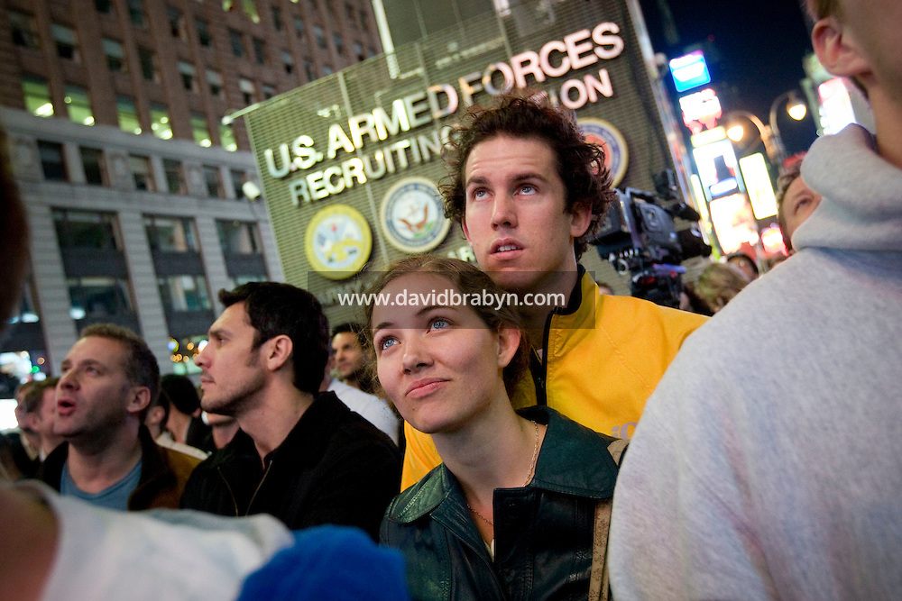 People listen to Barack Obama's acceptance in the 2008 US presidential election results on a giant screen on Times Square in New York, NY, United States, 4 November 2008.