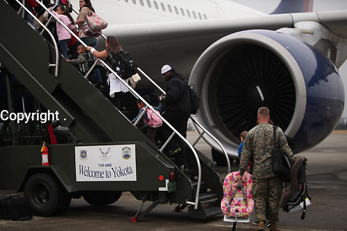 Dependents of service members stationed here board a plane, March 22, during a voluntary authorized departure. The Department of Defense is implementing the Department of State approved voluntary authorized departure for eligible Department of Defense dependents stationed on the island of Honshu, Japan. (U.S. Marine Corps Photo by 1st Lt. Jordan Cochran)