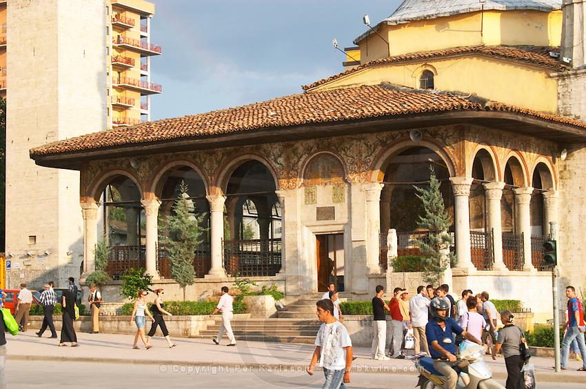 The Ethem Bey Beu Mosque. People on the street in front. The Tirana Main Central Square, Skanderbeg Skanderburg Square. Tirana capital. Albania, Balkan, Europe.