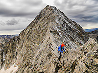 "A climber with the infamous 'Knife Edge"" just behind him on 14,131 foot high Capital Peak near Aspen, Colorado during a late season climb. The exposure on the Knife Edge is dramatic- the vertical walls drop from the narrow ridge several thousand feet to the valley below."