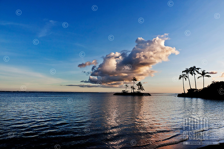 Seascape with tiny island and reflecting clouds at sunset.