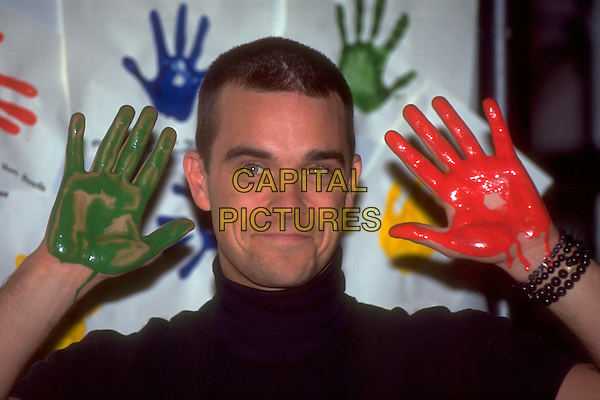 ROBBIE WILLIAMS.Convention Photocall at The Museum Of  Childhood,.London, England, 17th November 1999..portrait headshot hands paint covered funny black polo neck top.CAP/HT.©Hugh Thompson/Capital Pictures