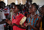 Women sing during Catholic Mass in Bunj, the host community for the Doro Refugee Camp in Maban County, South Sudan. Doro is one of four camps in Maban that together shelter more than 130,000 refugees from the Blue Nile region of Sudan. Jesuit Refugee Service provides educational and psycho-social services to both refugees and the host community. <br /> <br /> Misean Cara supports the work of JRS in the Maban camps and host community.