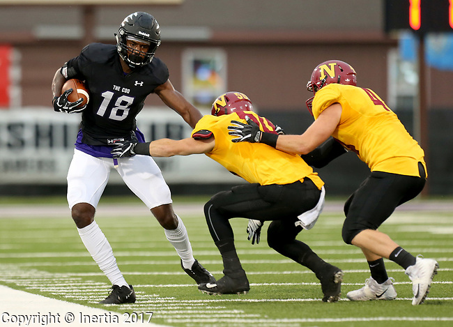 SIOUX FALLS, SD - SEPTEMBER 8: Anthony Holmes #18 from the University of Sioux Falls tries to slip the grasp of Cody Braeger #50 and Joe Gorghuber #44 from Northern State in the first half of their game Saturday night at Bob Young Field in Sioux Falls. (Photo by Dave Eggen/Inertia)