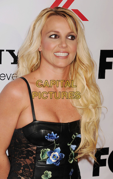 Britney Spears arriving at the 'The X Factor' Viewing Party Sponsored By Sony X Headphones at Mixology101 & Planet Dailies in Los Angeles, California, USA, December 6th, 2012. .portrait headshot smiling cleavage  black leather dress floral flowers embroidered red blue green bustier tanned lace .CAP/ROT/TM.©Tony Michaels/Roth Stock/Capital Pictures