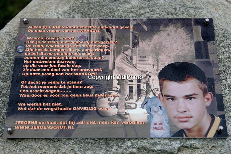 Foto: VidiPhoto..APELDOORN - Bij de voormalige onbewaakte spoorwegovergang aan de Savornin Lohmanstraat in Apeldoorn is dinsdag het eerste Nederlandse bermmonument voor treinslachtoffers onthuld. De .herdenkingsplaquette herinnert aan de twaalfjarige scholier.Jeroen Schut die op de onbewaakte spoorwegovergang in het donker en tijdens de stromende regen door een locomotief werd gegrepen en om het leven kwam. De NS is niet blij met het monument omdat men vreest dat passanten daardoor teveel worden afgeleid.