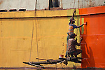 A pair of shipyard workers hang precariously from the side of a ship on the Buriganga River, Old Dhaka
