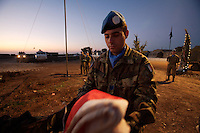 an  Italian soldier from the  Fifth  Lancieri of Novara regiment of the Italian Cavalry executes a flag ceremony that defines the end of the day's activities  in the UNIFIL Chama base in Southern Lebanon on Friday Dec 08 2006..Close to 1000 Italian peacekeepers operate in  the in Southern lebanon town of Chama, constantly patrolling their sector in search for illegal weapons in the country.