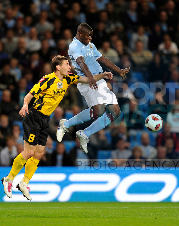 Micah Richards of Manchester City rises up to beat Laszlo Sepsi of Timisoara