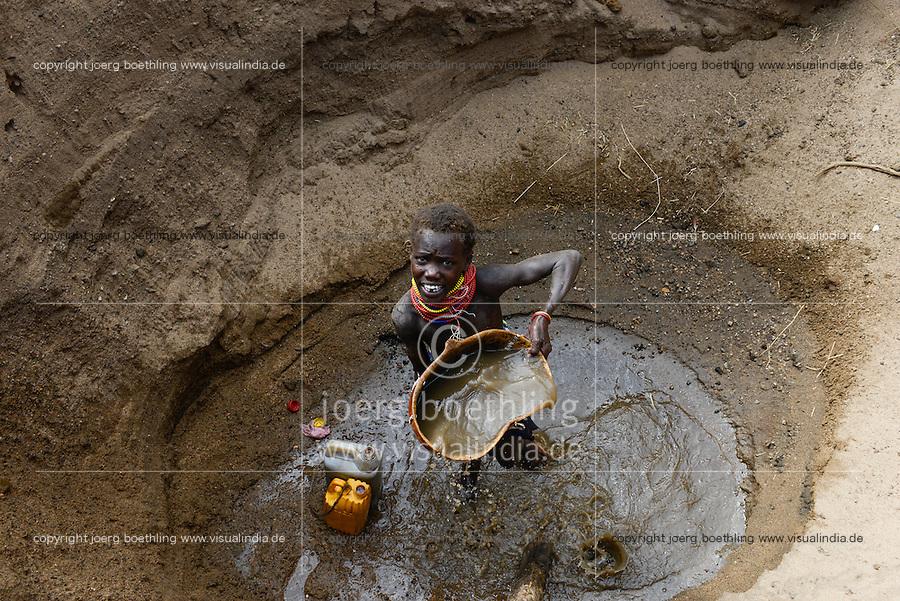 ETHIOPIA, Southern Nations, Lower Omo valley, Kangaten, village Kakuta, Nyangatom tribe, shepherds give water to their goats from water holes at dry river Kibish, girl Akiru / AETHIOPIEN, Omo Tal, Kangaten, Dorf Kakuta, Nyangatom Hirtenvolk, Hirten traenken das Vieh aus Wasserloechern am trocknen Fluss Kibish, Maedchen Akiru, 12 Jahre
