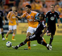 Julius James (2) of DC United tackles the ball away from Brian Ching (25) of the Houston Dynamo during their game at RFK Stadium in Washington, DC.  Houston defeated D.C. United, 3-1.