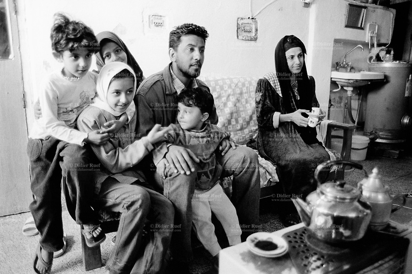 Iraq. Baghdad. Al Sadr City. Family Abo Basheer sits on a couch. The mother and two girls wears the hidjab on their heads which cover their hair. The word hijab (or hidjab) refers to both the veil covering the head and traditionally worn by muslim women (Islamic headscarf), but also the  modest muslim styles of dress in general. 20.02.04  © 2004 Didier Ruef