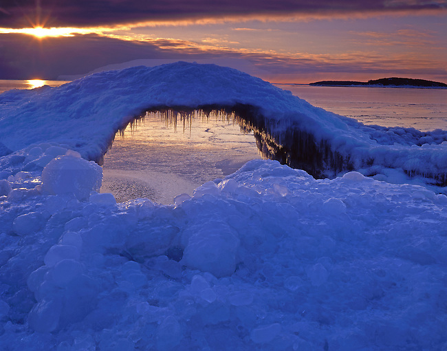 The sun rises over the frozen surface of Lake Superior and through an arch of ice on the shore, Presque Isle Unit, Escanaba State Forest, Marquette County, Michigan