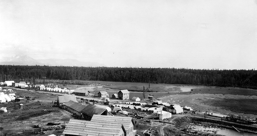View of the temporary railroad construction town consisting of tents and a few buildings along Ship Creek in Anchorage, Alaska, 1915.  The Montana Pool Room is visible near the left edge of the image. This image was probably taken within a few days of Capps arrival in Anchorage on June 14, 1915.  Photo by S.R. Capps, 1915, U.S Geological Survey Photo Library.