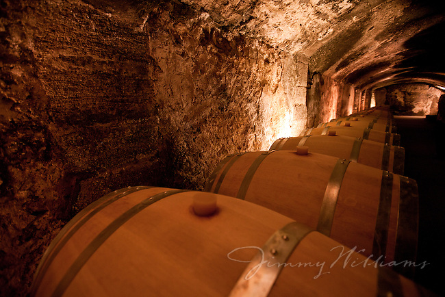 Barrels of wine aging in the cellars of Château La Nerthe Vineyard, France